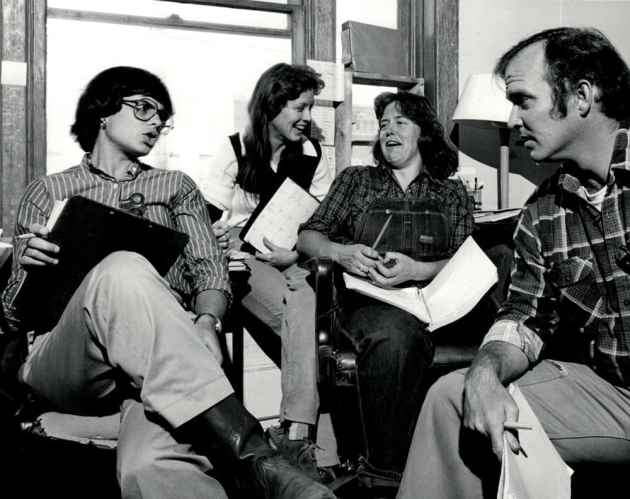"""The High Country News staff has a meeting in the early 1980s, while the magazine was still based in Lander. Left to right; Jill Bamberg (publisher), Carol Jones (associate editor), Kathy Bogan (designer), and Dan Whipple (editor). """"I think I still have that shirt,"""" said Whipple. (courtesy Dan Whipple)"""