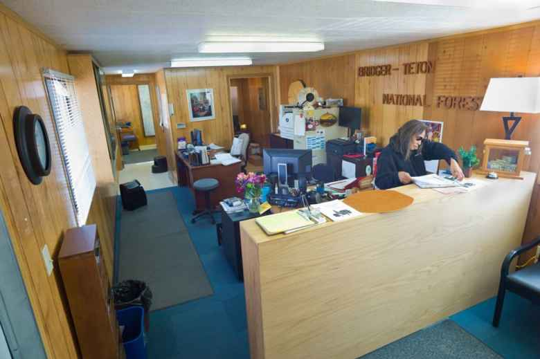 Bridger-Teton National Forest veteran Dorothy Neckels's new front desk is in a trailer at the Jackson forest headquarters site. The agency hopes the sale of administrative property on a main town street will fund a new headquarters building. (Angus M Thuermer Jr/Wyo/File)
