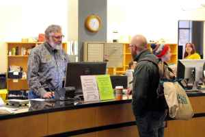 Harry Whitlock, University of Wyoming library specialist, assists a student at the Coe Library reference desk. The hiring freeze for all state employees is expected to save $16 million to $18 million dollars, or 10 percent of the $159 million deficit for 2016. (Gregory Nickerson/WyoFile)