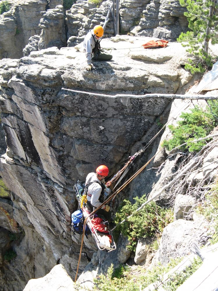 Park Rangers Gabe Gassman (bottom) and Sarah Strehle simulate a litter hoist in Lewis River Canyon. (Phil Strehle)
