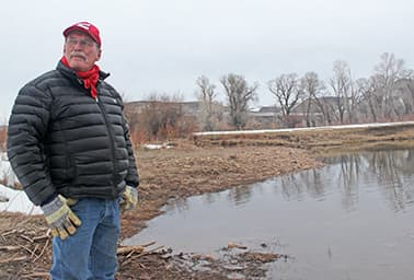 Pat O'Toole stands at the confluence of Battle Creek and the Little Snake River, where he plans to restore willows and cottonwood trees. Photo by Phil Taylor.