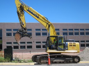 A backhoe operator prepares to bust and scoop up another section of sidewalk at Kelly Walsh High School in Casper. Construction worker Juan C. Avalos of Colorado died in a workplace accident at the construction site June 17, 2016. (Dustin Bleizeffer/WyoFile)