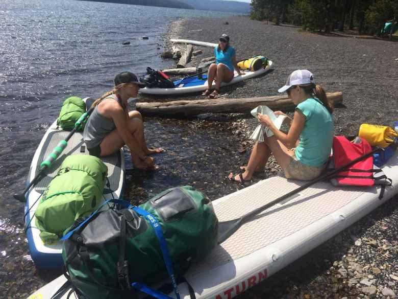 Ashley Chadwick checks the map with Jessica Seitz and Alicia Maggard on Shoshone Lake. Traveling by paddleboard takes a lot longer than canoe or kayak. (Kelsey Dayton/WyoFile)