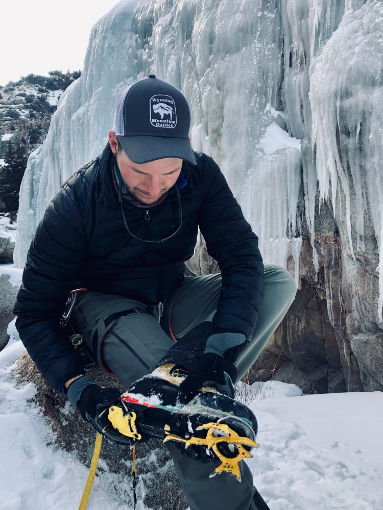 Wyoming Mountain Guides assistant guide Taylor Nielson sports a Bison Logo trucker hat while gearing up for ice climbing in Shell Canyon, Wyoming.