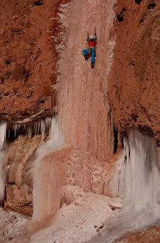 Kaitlin Dooling climbs the red-streaked ice of Ten Sleep Falls in lower Ten Sleep Canyon