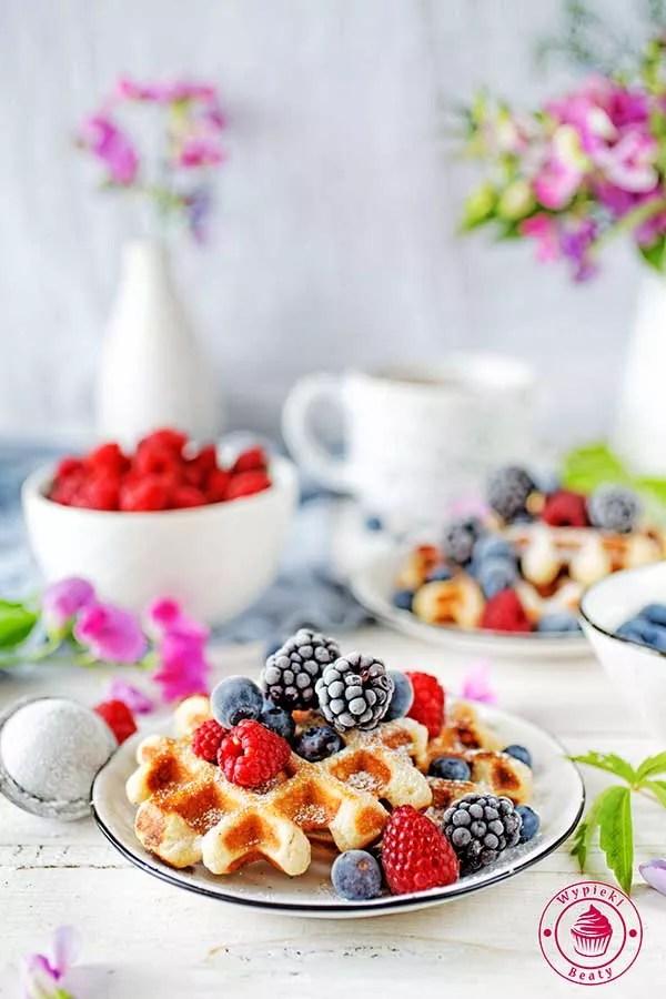 śniadanie z goframi, owocami, borówkami i malinami na talerzu