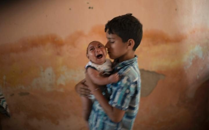 10-year-old Elison nurses his 2-month-old brother Jose Wesley