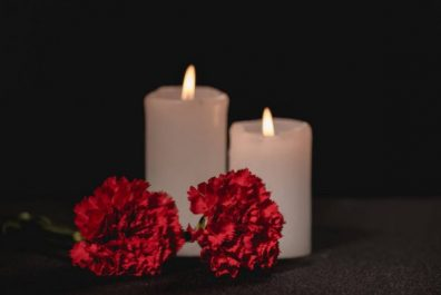 depositphotos_429855696-stock-photo-red-carnation-flowers-and-candles