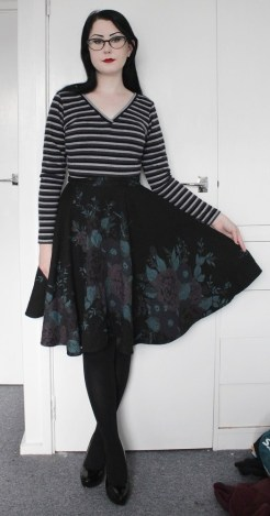 Striped long sleeved V-neck top. Black full circle skirt with quilting detail on the fabric and painted-look floral pattern.