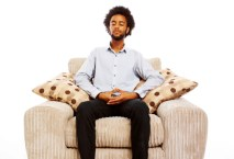 content young man sitting meditating in comfy chair on white