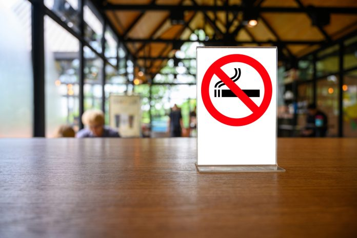 no smoking sign with shopping place background on wooden table