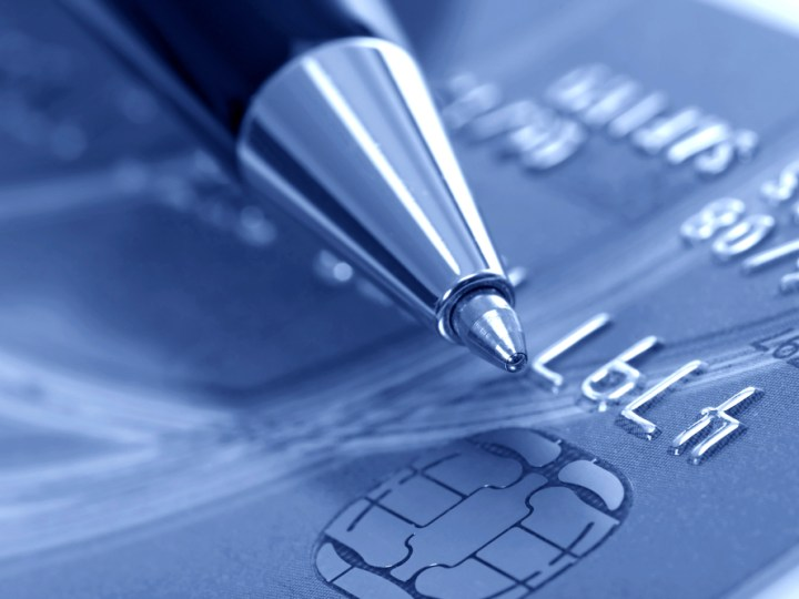 Pen atop of a blurred credit card image