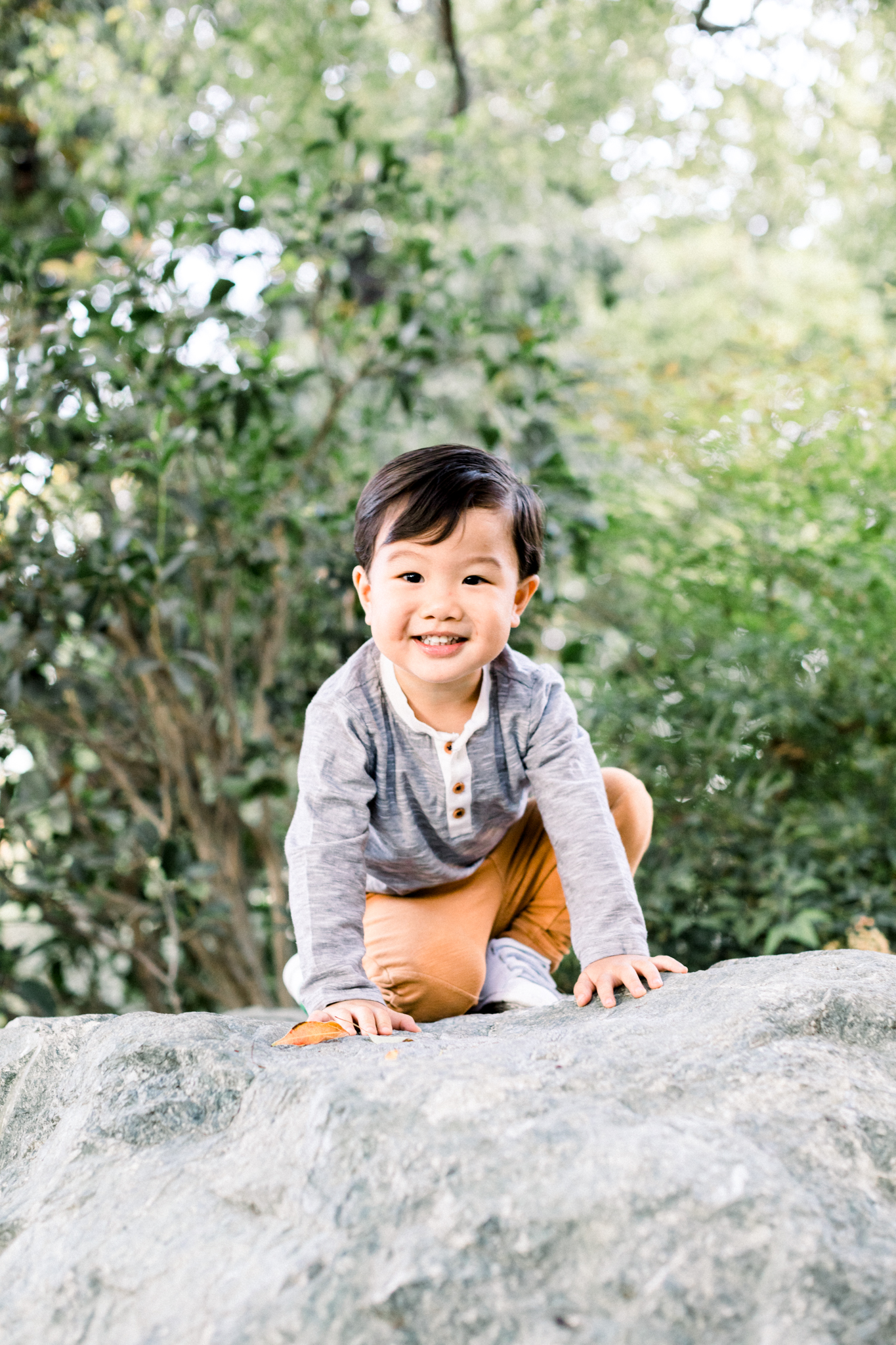 A little boy posing and smiling on top of a rock.