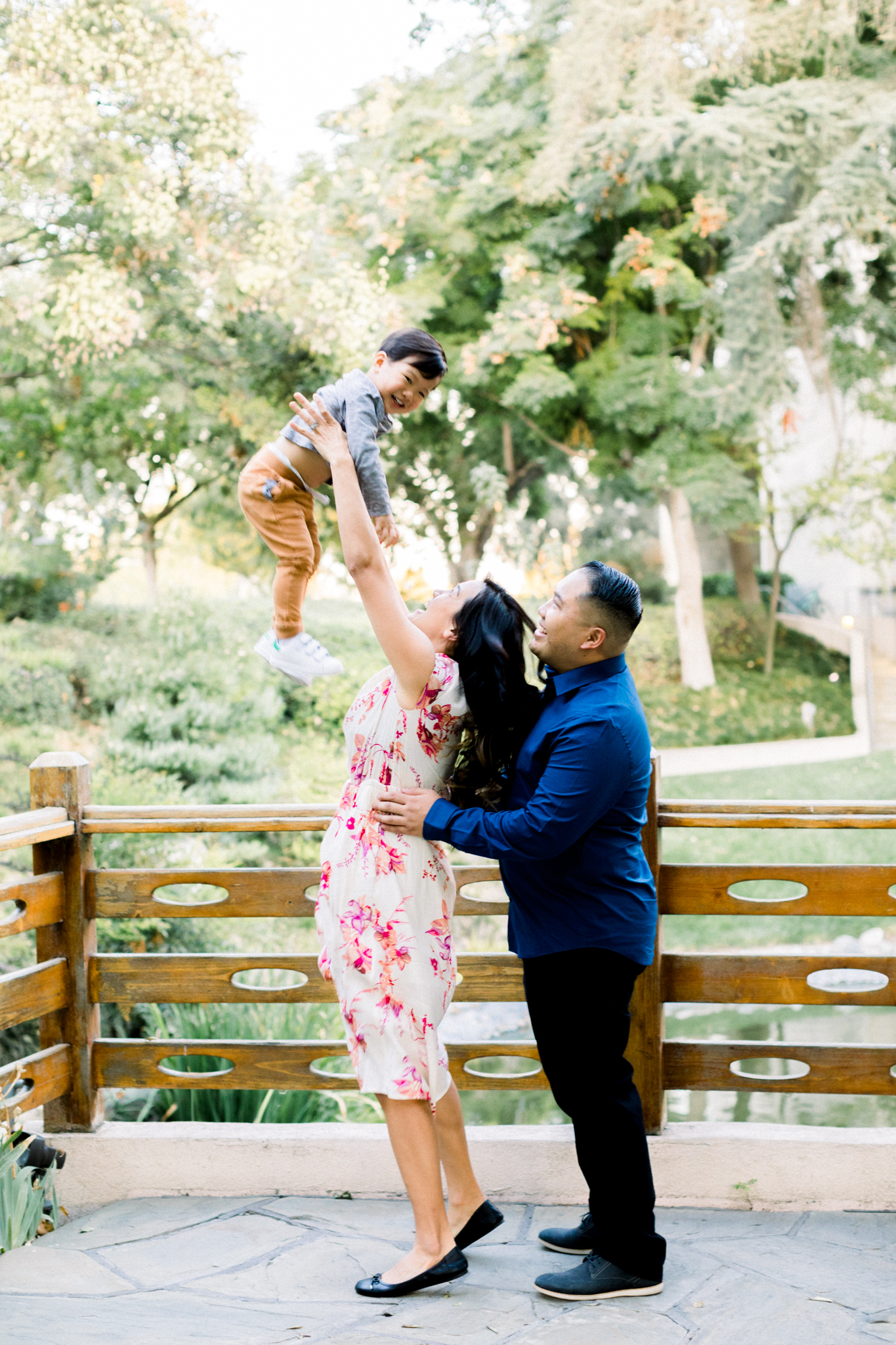 Two parents raising their child in the air during their family photography session in Pomona.