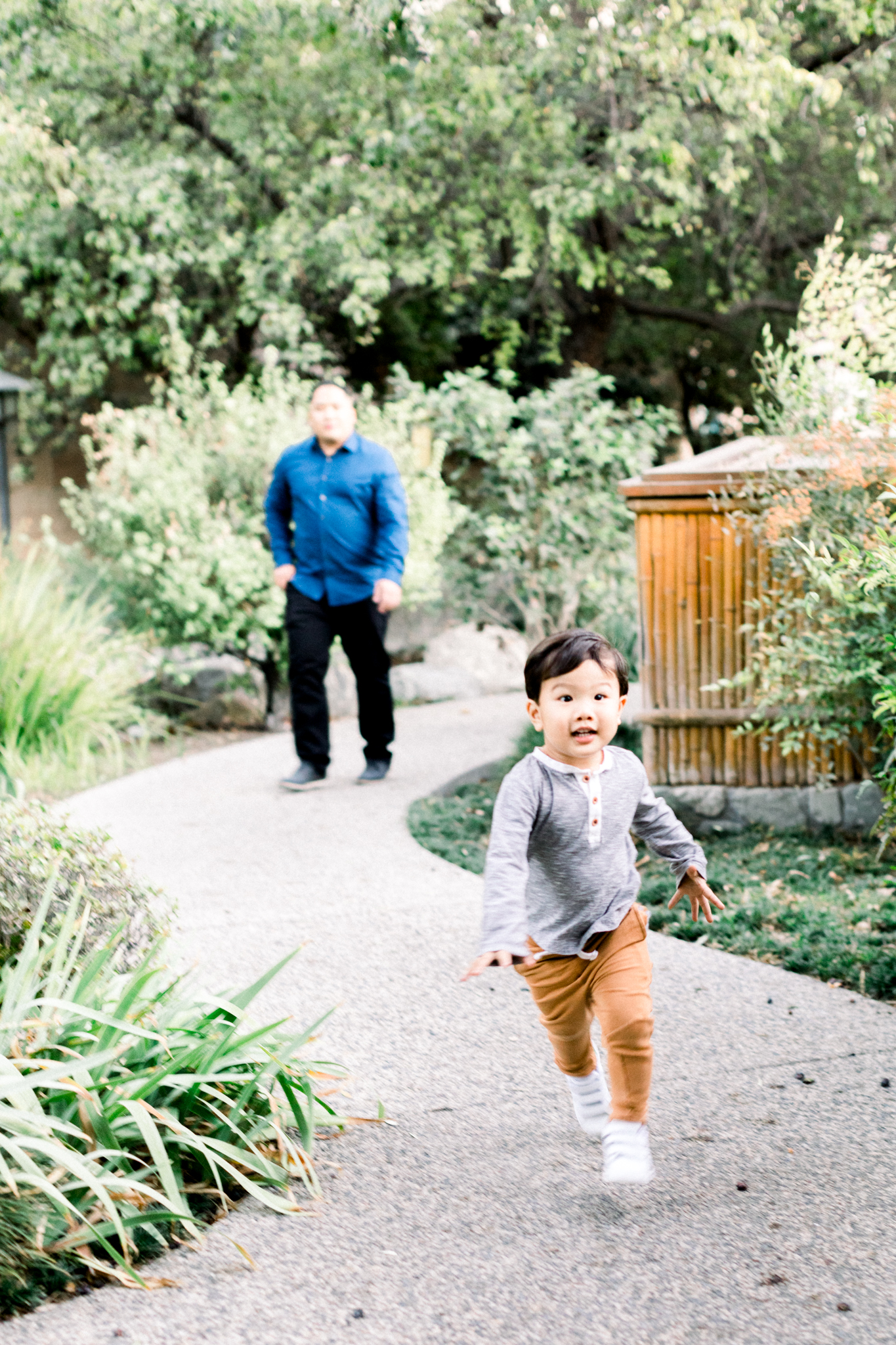 A young boy running down a path in Cal Poly during his family photography session.