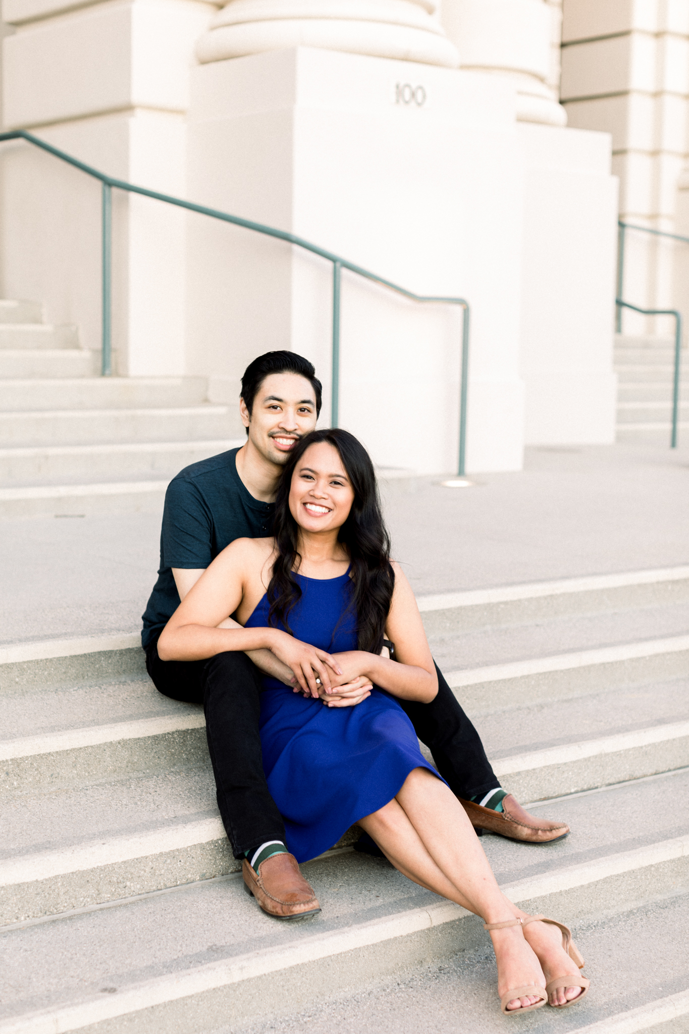 An engaged couple sitting in front of the doors of the Pasadena City Hall.