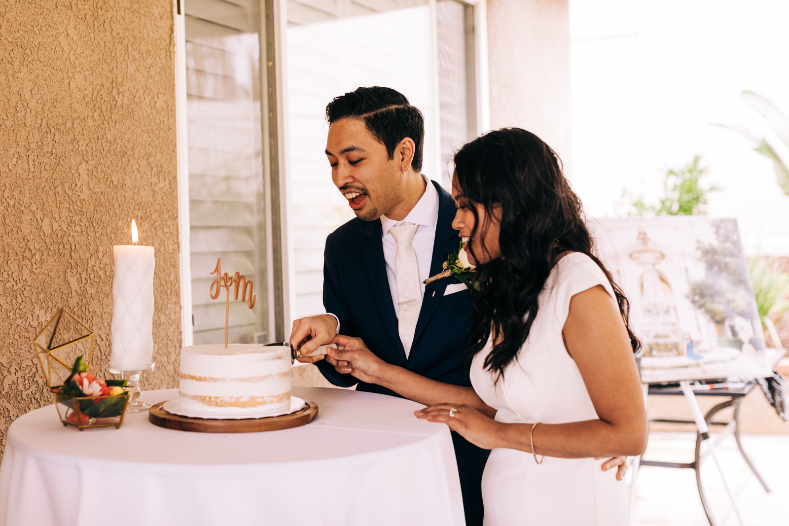 A bride and groom cutting their cake during their micro-wedding in Southern California.