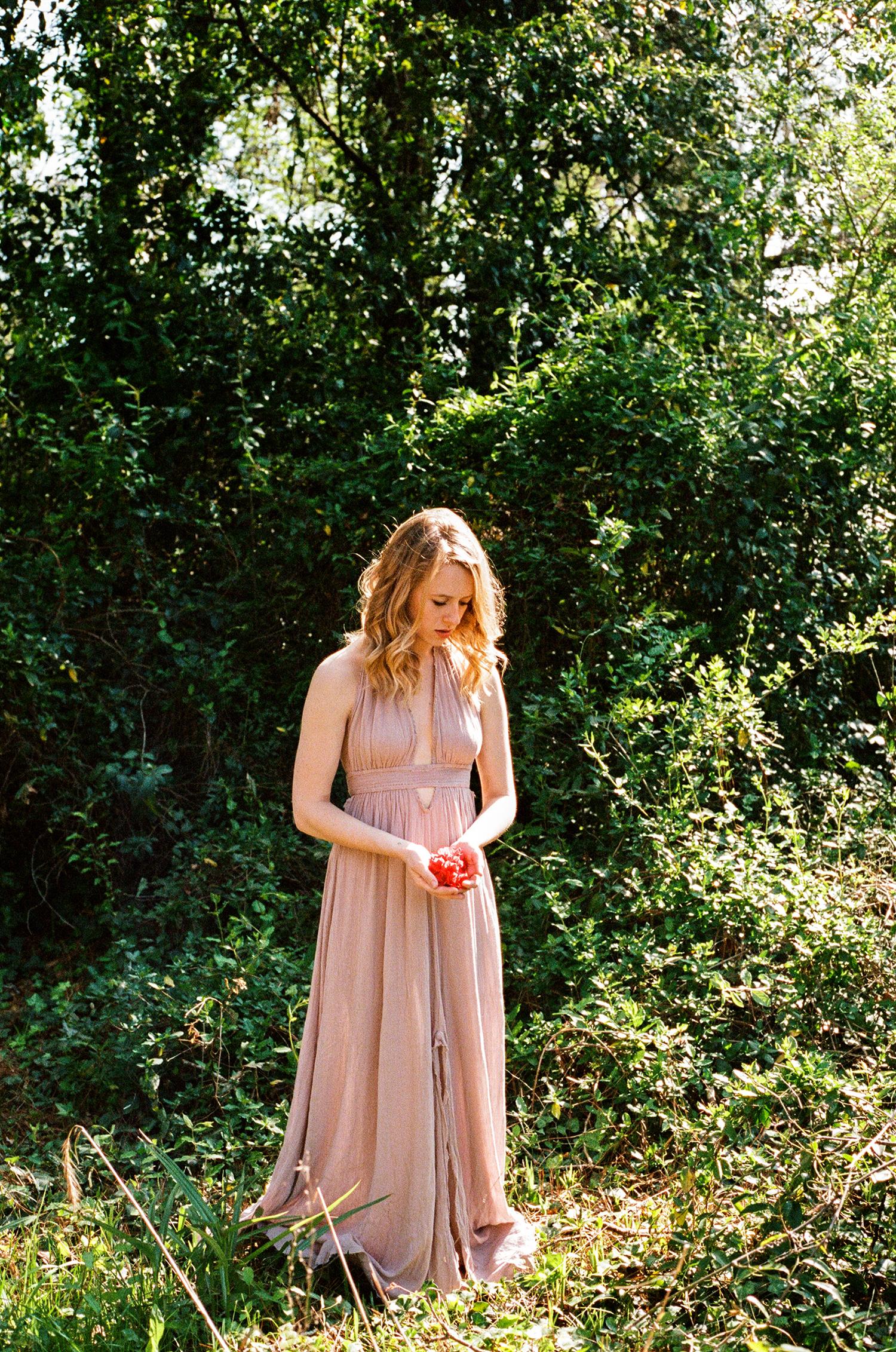 girl in long dress holding flowers