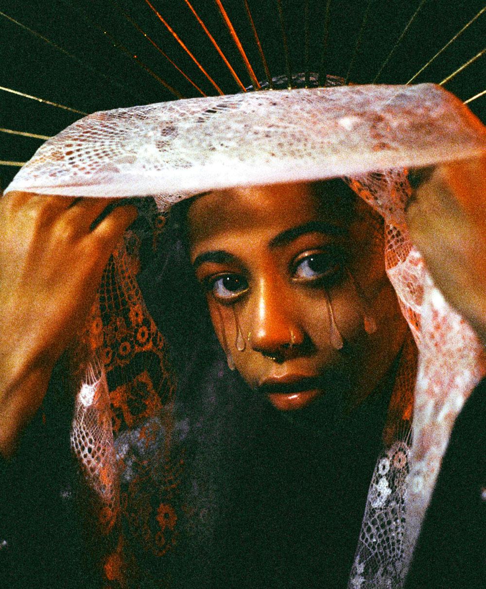 35mm film photo of woman lifting white veil