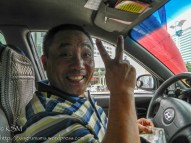 Chinese taxi driver flashing the peace sign and smiling broadly.