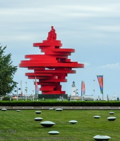 The bright red sculptures axis forms a vertical line.