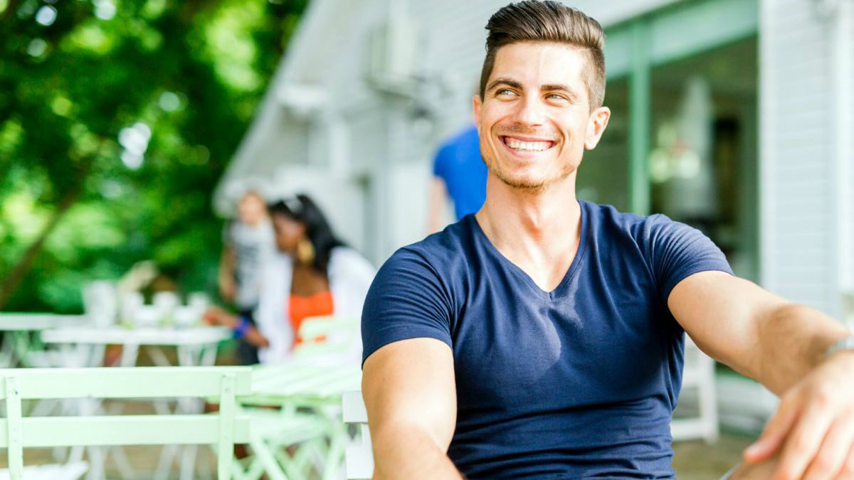Portrait of a handsome man sitting on a chair and a smiling outdoors