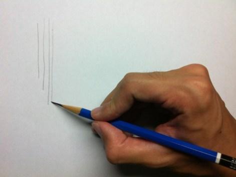 鉛筆持ちで縦の線を描く
