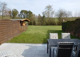 Blick in den Garten mit Gartenhütte und unverbaute Aussicht auf den Deich.