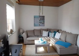 Der gemütliche Wohnbereich bietet mit der neuwertigen Couch genug Platz zur Erholung.