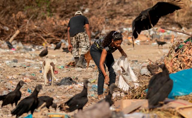 Venezolanos disputan restos de comida con buitres en un basurero en Paracaima