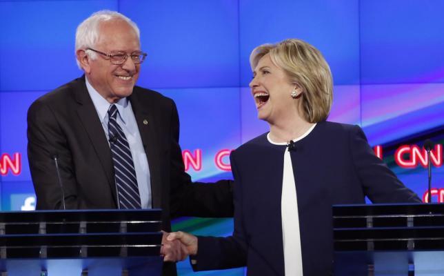 10月14日、13日夜に行われた来年の米大統領選をめぐる民主党の候補者討論会では、前国務長官のヒラリー・クリントン氏(67・写真右)がアナリストの高評価を獲得した。写真は討論会の会場で、対立候補のサンダース上院議員と握手を交わすクリントン氏。13日撮影(2015年 ロイター/Lucy Nicholson)