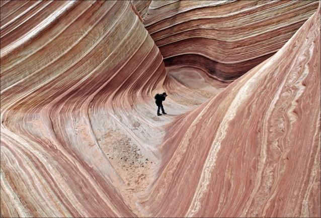 fotografó intenta captar la onda de la roca
