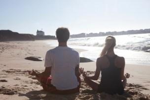 浜辺でヨガポーズするカップル