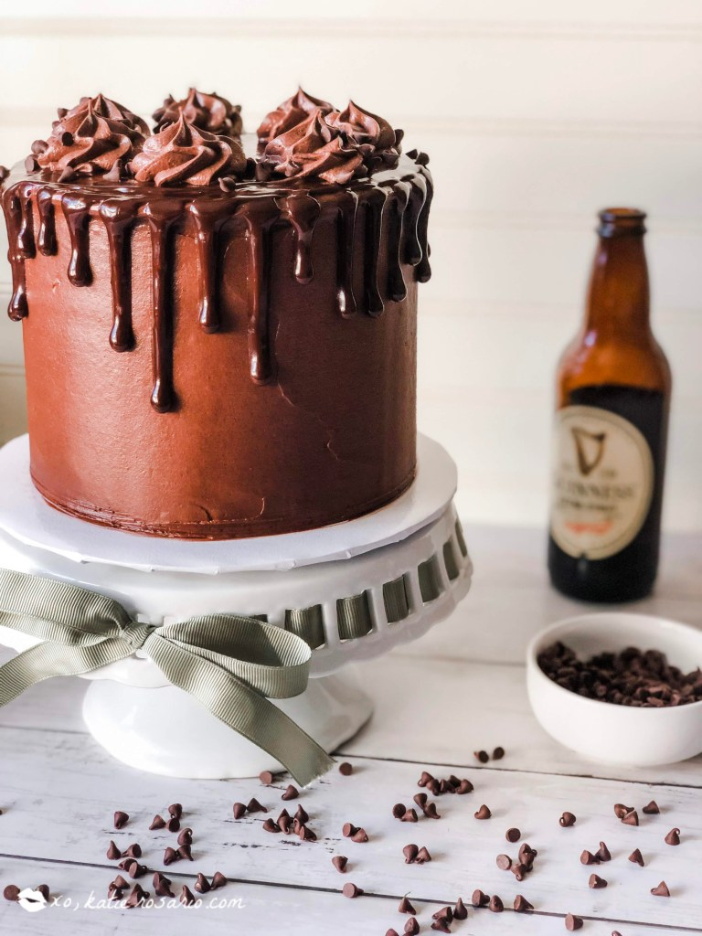 This Chocolate Guinness cake is rich and decadent especially with a smooth ganache drip running down the sides of the cake! Guinness is a dark rich beer that lends itself to pair perfectly with chocolate. The sweetness of the chocolate compliments the bitter notes of the Guinness beer. Guinness is used in the cake and the frosting so you know it'll taste delicious! #xokatierosario #chocolateguinnesscake #chocolatecakerecipe #chocolatecakefromscratch