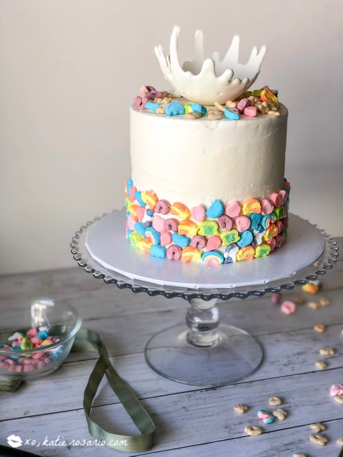 This cake is perfect for celebrating St. Patrick's Day, its colorful and sweet and made with the Lucky Charms cereal. What's unique about this cake is how we'll make cereal milk. The famous Lucky Charms marshmallows are decorating the outside of the cake and a whimsical white chocolate milk spill topping the cake. #xokatierosario #luckycharmsrecipes #luckycharmscake #luckycharmsdesserts