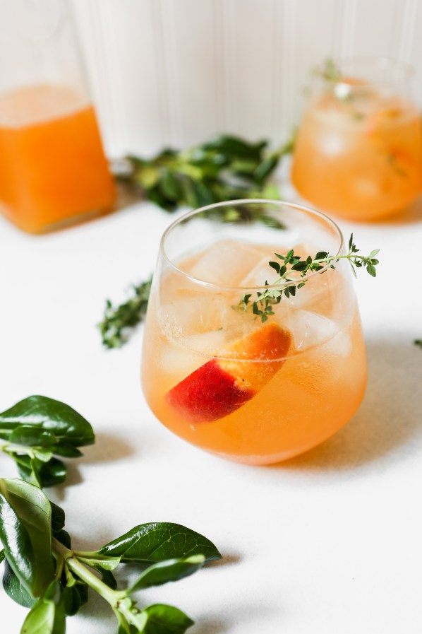 Peach Thyme Spritz | These sparkling drinks are fantastic for summer entertaining. Whatever sparkling drinks you choose to make this summer, your thirst will be quenched, and you'll stay relaxed and happy in the summer heat. Here are 14 Sparkling Drinks That'll Keep You So Refreshed! #xokatierosario #sparklingdrinks #sparklingcocktails #sparklingnonalcoholicdrinks #summerentertaining