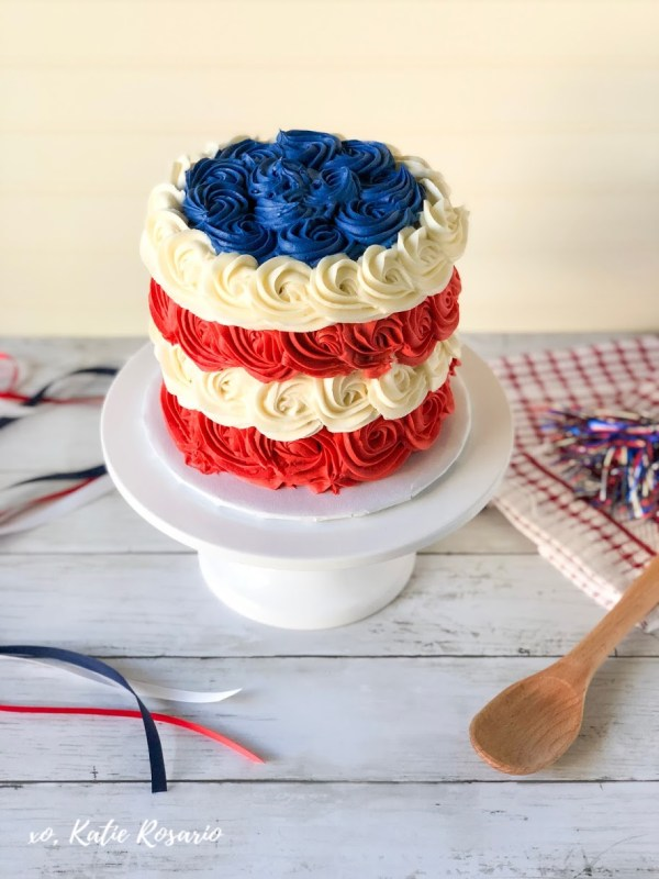 Make this 4th of July festive with this fun Red, White & Blue Rosette Cake! This red, white and blue rosette cake is a simple vanilla cake made with creamy buttercream. The cake layers are individually colored and flavored for a perfect 4th of July surprise. This red, white and blue cake is great for beginner bakers. #xokatierosario #fourthofjulycake #redwhitebluecake #rosettecakeideas #summercakeideas