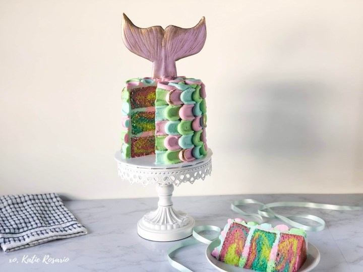This mermaid buttercream cake is made with tender vanilla cake layers and creamy vanilla buttercream that looks like mermaid scales. The cake batter is colored with purple, blue and green gel food color that are swirled together for a beautiful mermaid cake. It's a perfect cake for birthday or summer parties. This mermaid cake is sure to impress and make everyone happy! #xokatierosario #mermaidcake #mermaidpartyideas #cakedecoratingtipsandtricks