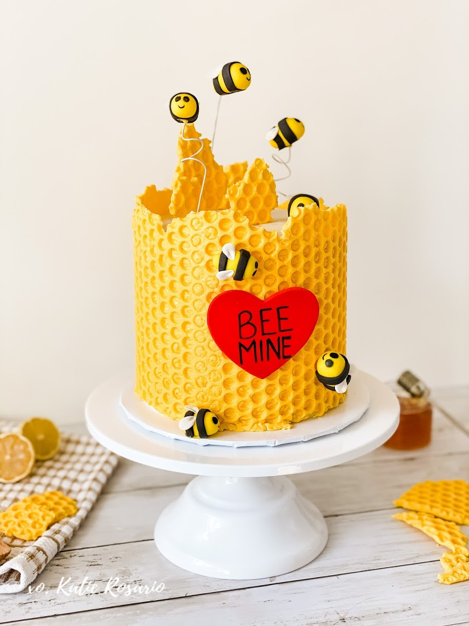 Looking for a unique Valentine's Day cake that looks almost too pretty to eat?! This Bee Mine Cake is super creative and perfect for your Valentine! This Bee Mine cake is made with honey lemon cake layers filled with creamy honey lemon buttercream. I genuinely believe that all bakers can make this cake even beginner bakers. If you are willing to try, you'll succeed! #xokatierosario #beecake #beemine #valentinesdaycake #honeycombcake