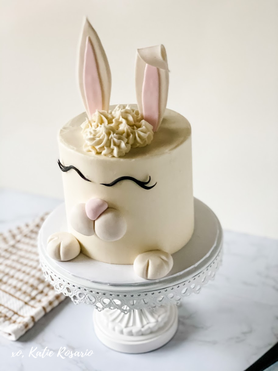 This spring season make this bunny cake, which is perfect for Easter Sunday! This Bunny cake is made with fluffy orange-scented almond cake layers and creamy vanilla buttercream. That is decorated with fondant to look like a cute little bunny. What I think you'll love most about this cake is that you can do this with friends or even your kids. #xokatierosario #bunnycake #eastercake #cakedecoratingtips #animalcake