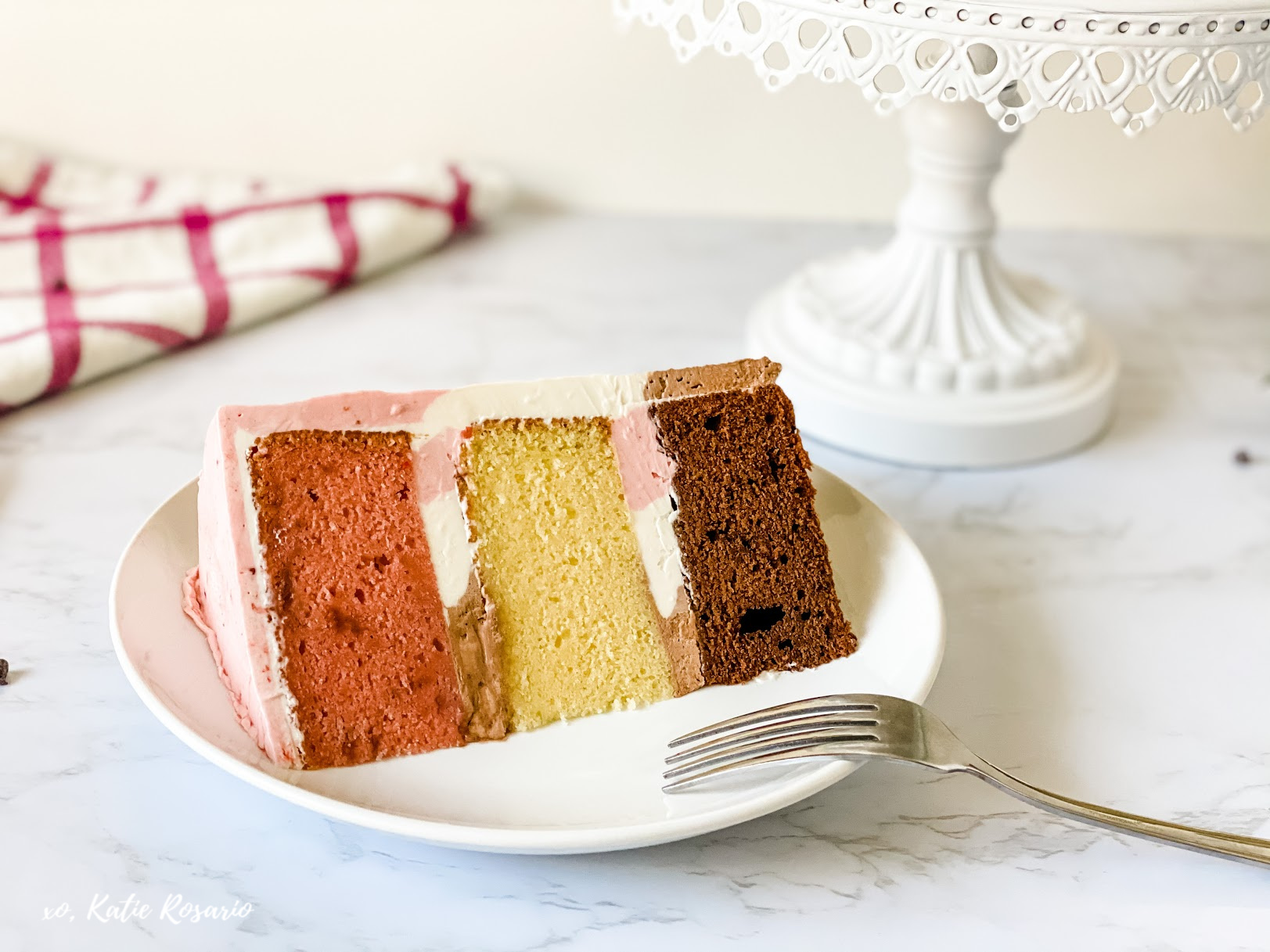 Is the summer heat getting you down? Learn how to turn a classic ice cream treat into a rich and decadent Neapolitan Cake. You'll see this is a simple design cake, and that's done on purpose, so you can focus on building the flavors and perfecting the technique of smoothing the sides of the cake. #xokatierosario #neapolitancake #neapolitancakerecipe #icecreamcake #cakedecoratingtips