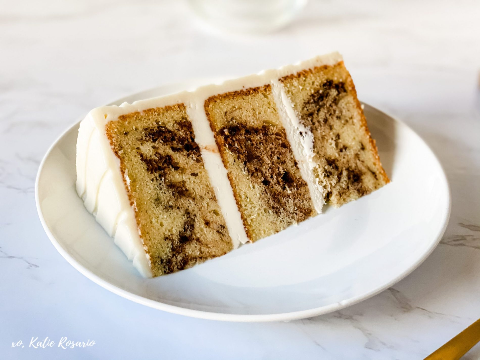 Looking for an ooey-gooey Christmas cake that all your family and friends will love? This Cinnamon swirl cake is made with light, and fluffy vanilla cake with cinnamon filling swirled inside topped with cream cheese buttercream. The holidays may look different this year, but this Cinnamon Swirl Cake will bring everyone together. #xokatierosario #cakedecoratingtips #cinnamonswirlcake #cinnamonroll #christmascake