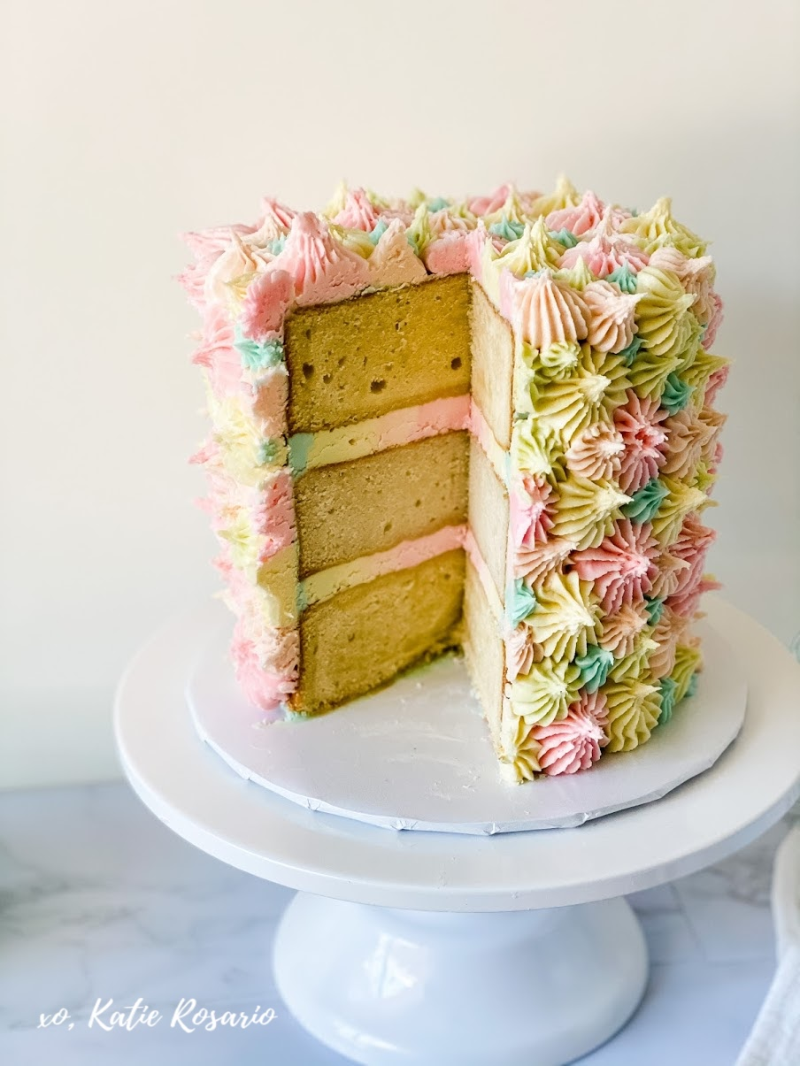 Learn how to make this Pretty Pastel Cake by Katie Rosario that's made with moist vanilla cake layers and filled with creamy pastel buttercream. Pretty pastel cakes can be eye-catching with a bit of texture. Even with such a simple pattern, this cake is artfully whimsical. This is a super fun cake to make that would be amazing to make with your kids or friends. It can be messy and make so many memories. Go to xokatierosario.com to get the full tutorial! #xokatierosario #katierosariocakes #pastelcake #springcake #coralcake #cakedecoratingtips