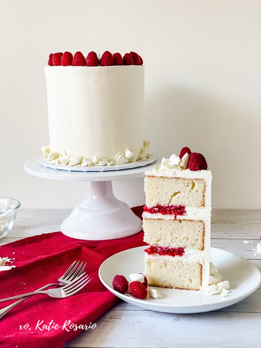 This white chocolate raspberry cake is the perfect balance of tart & sweet! Its soft white cake layers and tart raspberry filling make it irresistible! Created by Katie Rosario, XOKatieRosario creates beautiful cake decorating techniques that are easy for beginners and strategically designed for any home baker. #xokatierosario.com #xokatierosario #katierosariocakes #cakedecoratingcourse #whitechocolatefrosting #whitechocolateraspberry