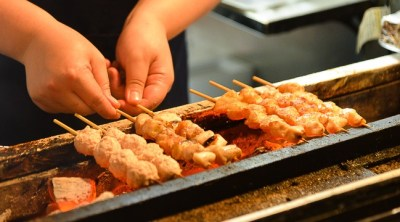 Chef preparing yakitori on grill