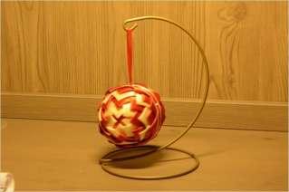 Bombka choinkowa czerwono - kremowa na tle szafki (za szafką jest przepiękne, białe tło, niestety, jest za szafką)