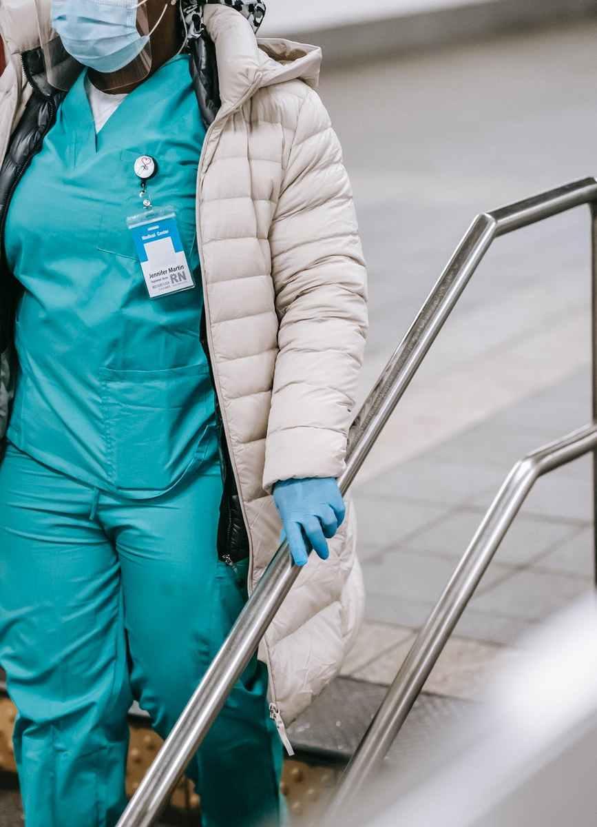 crop black nurse going downstairs in underground passage