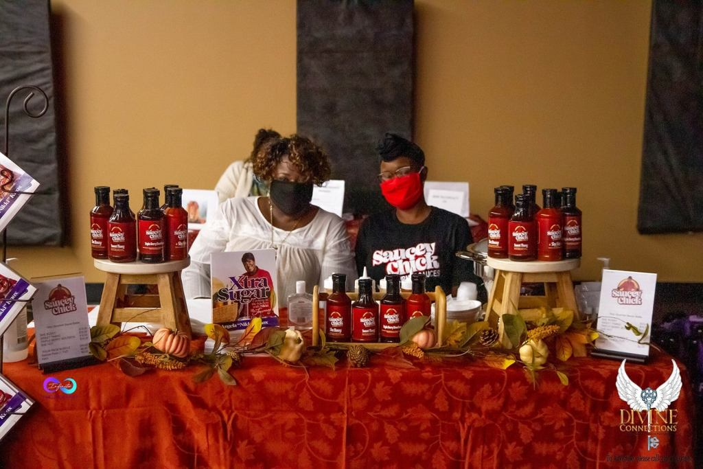 Photo of Chef Nikki and a team member with masks on set up at an event, surrounded by Saucey Chick sauces and the XtraSugar cookbook