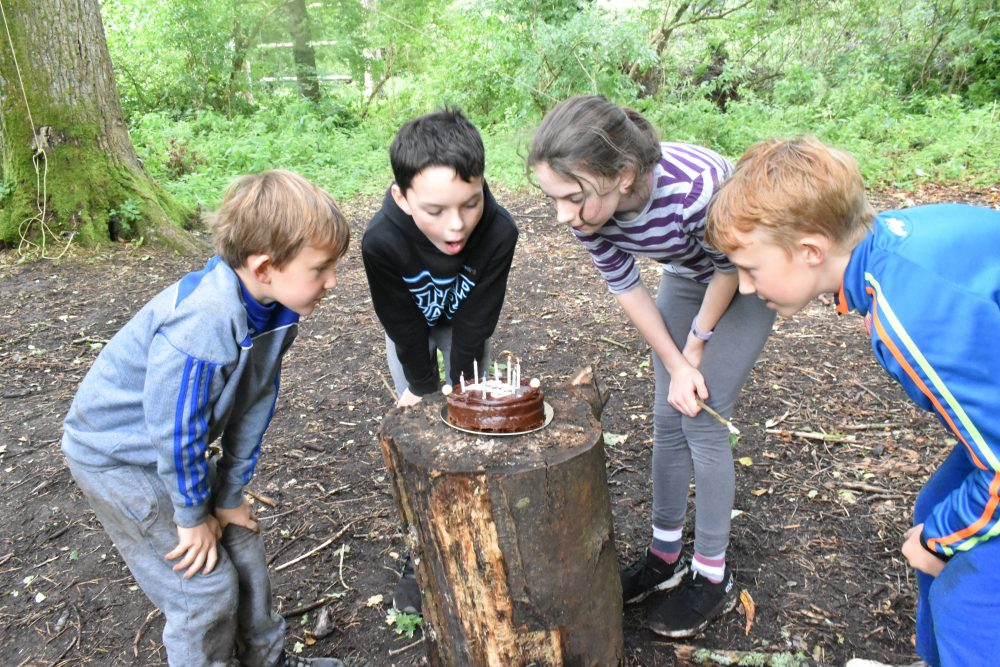 Kids gathered around a birthday cake blowing out the candles during their bushcraft birthday party hosted by Xtreme.ie.