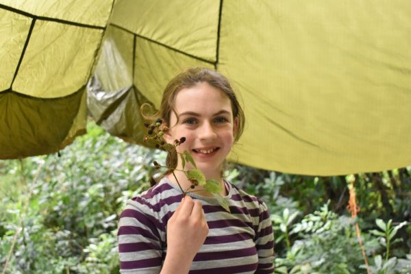 A girl at Xtreme.ie's Bushcraft Birthday Parties enjoying foraging for different flowers and leaves in the forest.